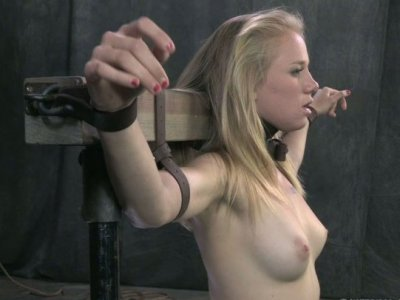 Wearing a leather collar Tracey Sweet gets attached to the wooden bar